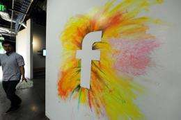 An employee walks past one of the many wall graffitis at the Facebook headquarters in Menlo Park, California
