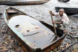 An indigene of Bodo, Ogoniland region in Rivers State, tries to separate with a stick the crude oil from water in a boat