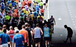 A runner stops to stretch a muscle while  the pack run along the Embankment during the 2012 London marathon