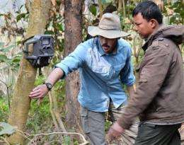 A scientist sets a motion-activated camera  in a national park in Nepal