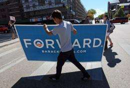 A supporter of US President Barack Obama, carries a sign across the street prior to the presidential debate in Denver