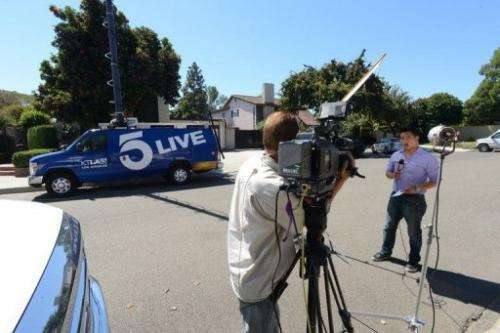 A TV journalists reports from outside of a house in Cerritos, California