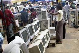 A used-computer vendor attends to a buyer at Lagos' computer village in 2006