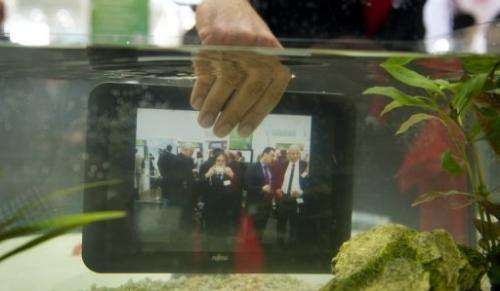 A waterproof tablet PC from Fujitsu is seen lowered into a fish tank at CeBIT