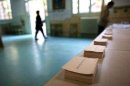 A woman arrives to pick up ballots prior voting at a polling station in Paris