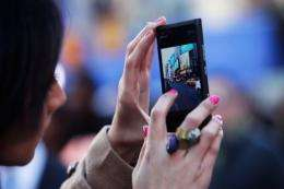 A woman takes a picture of Times Square on her cell phone