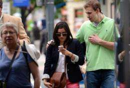 A woman uses her smartphone while crossing street