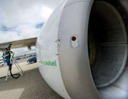 A worker fuels a KLM aircraft which runs on a blend of biokerosene derived from cooking oil and traditional jet fuel