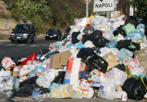 Cars pass by mountains of uncollected trash in Naples