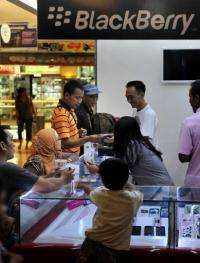 Customers browse over Blackberry smartphones on display at a shop in Jakarta