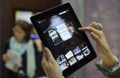 Customers try out an eBook reader app on an Apple iPad at the Leipzig Book Fair on March 15, 2012 in Leipzig, Germany