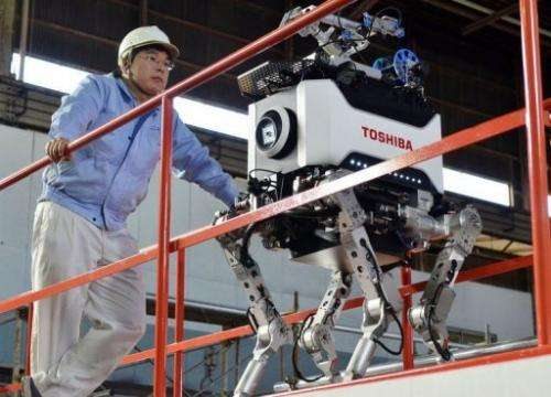 Engineers inspect Toshiba's four-legged robot