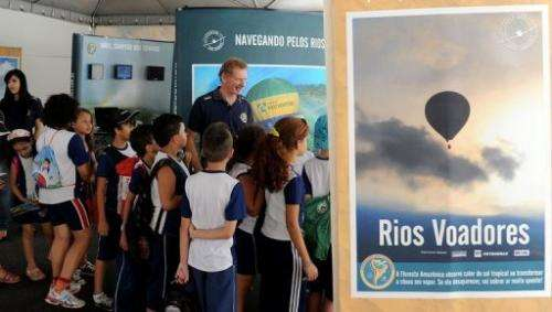 "Gerard Moss (C) talks to children during an exhibition of his ""Rios Voadores"" (Flying Rivers) project"