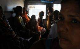 Indian women and children waiting inside a train carriage at a railway station in New Delhi, in July