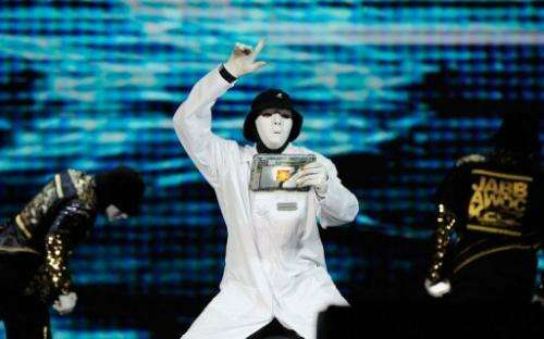 Members of the JabbaWockeez dance crew perform holding a tablet with the Qualcomm Snapdrogan processor