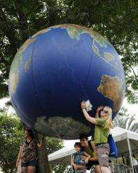 People pose with a giant globe