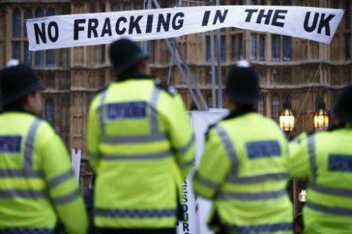 Police watch demonstrators protesting against 'fracking' for shale gas in London on December 1, 2012