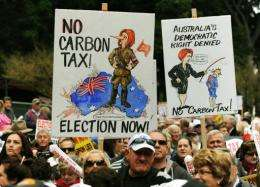 Protesters hold placards as they attend a no carbon tax rally in Sydney