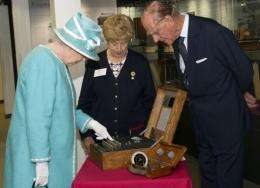 Queen Elizabeth II (L) and Prince Philip look at the Enigma codebreaking machine at Bletchley Park in 2011