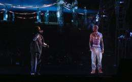 Rapper Snoop Dogg (L) and a hologram of deceased rapper Tupac Shakur (R) perform onstage during music festival