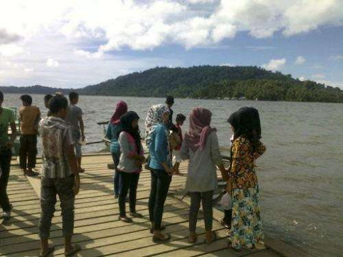 Residents of the remote Simeuleu island near Aceh observe the sea level in their bay