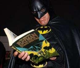 Superhero Batman reads a Batman comic book