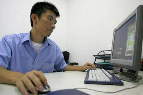 Technician is seen working on his desktop PC at a foreign-invested software company in Chengdu, on July 14, 2006