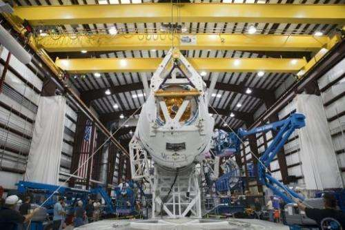 Technicians attach the Dragon capsule to a Falcon 9 rocket at the SpaceX facility in Florida