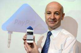 """The PayPal Here system uses a triangular """"dongle"""" card reader that plugs into mobile devices"""