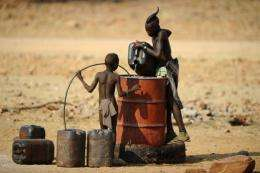 Two Himba boys pour water into a tank in 2010 in the village of Okapare, near Opuwo in northern Namibia