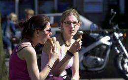 Two young women enjoy ice cream on a sunny day in Brussels