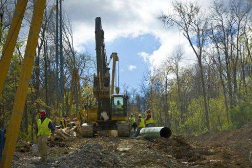 Workers lay the pipes of a gas pipeline outside the town of Waynesburg