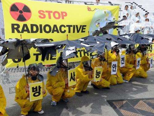 Activists wear yellow raincoats and gas masks and hold torn umbrellas during a rally in Seoul on April 21, 2011 to oppose nuclea