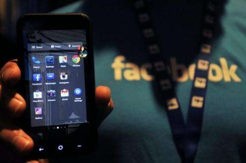A Facebook employee displays an HTC phone with the new Home operating system at Facebook's headquarters, April 04, 2013