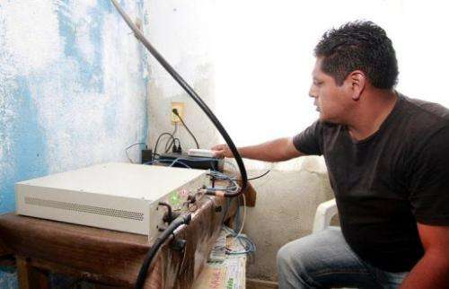 A local resident operates the equipment enabling mobile communications in Talea de Castro in Mexico, on August 17, 2013