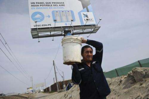 A man carries a bucket full of water near a billboard that works as a dehumidifier in Bujama, March 15, 2013