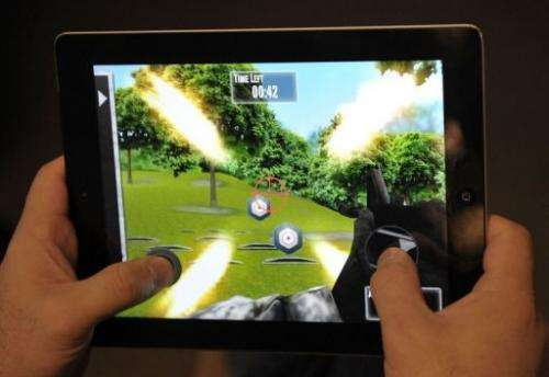 "A man plays the newly released National Rifle Association (NRA) iPhone/iPad app, ""NRA: Practice Range"""