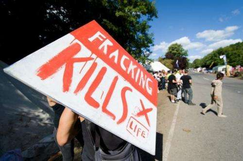 "An anti-fracking protester holds a ""Fracking kills"" poster outside a test drill site in Balcombe on August 20, 2013"