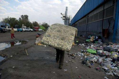 "A scavenger carries a mattress at the ""Bordo Poniente"" garbage dump in Mexico City on January 18, 2012"