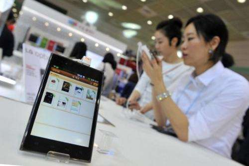 """A South Korean woman inspects LG's smartphone """"Optimus Vu"""" during an IT show in Seoul on May 15, 2012"""
