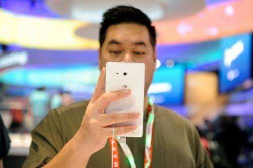 A visitor tries out a Huawei Ascend Mate ''phablet'' at the 2013 International CES in Las Vegas, on January 9, 2013