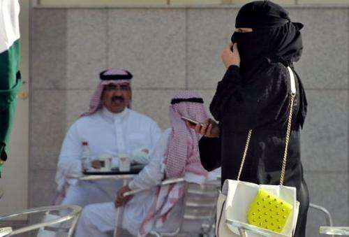 A woman holds a mobile as she walks past a coffee shop in the Saudi capital Riyadh on June 17, 2013