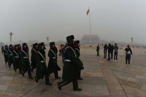 Chinese military policemen march through Tiananmen Square during heavy air pollution in Beijing on January 30, 2013