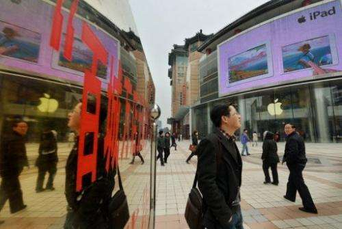 Chinese tourists walk past an Apple store in Beijing on March 29, 2013