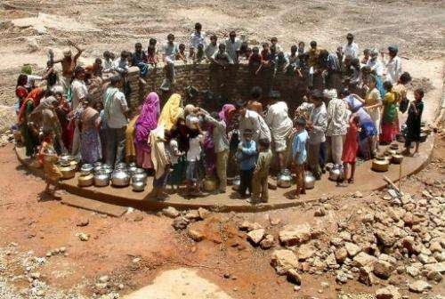 Indian villagers gather around a well to fill their pots with water during a drought in Gujarat on June 6, 2003