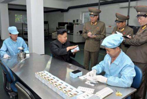 N.Korean leader Kim Jong-Un (C) inspects 'Arirang' smartphone at the May 11 factory, on August 11, 2013