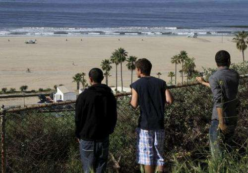People watch a beach in Santa Monica on March 11, 2011, after tsunami warnings were issued along the US west coast