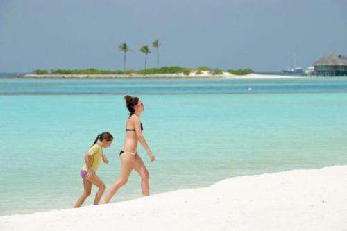 Tourists walk along a beach of the Paradise Island Resort and Spa in the Maldives on February 14, 2012
