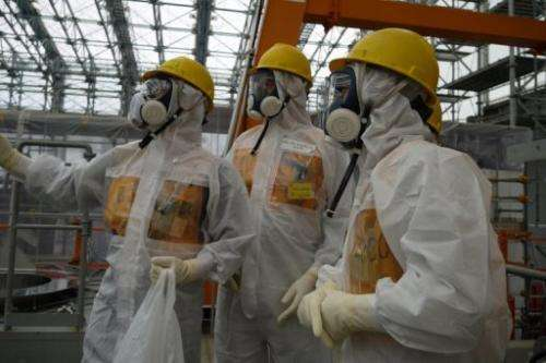 Workers inspect the Fukushima Dai-ichi nuclear power plant on September 12, 2013