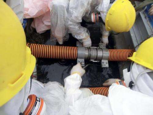 Image provided by TEPCO on October 9, 2013 shows workers checking pipe joints at a decontamination facility at the Fukushima nuc